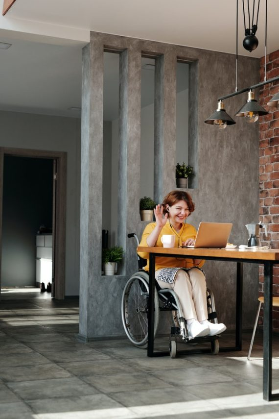 Woman in wheelchair smiling and waving at laptop