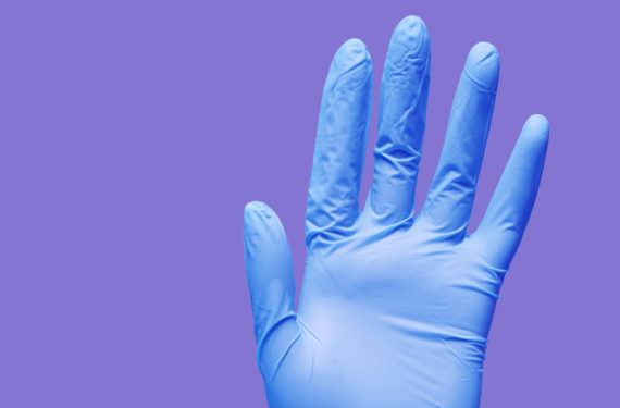Hand wearing blue, power-free nitrile gloves